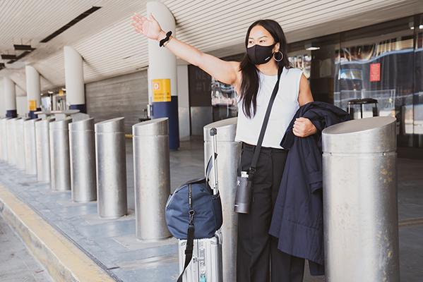 masked woman hailing cab